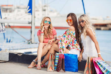 Three beautiful girlfriends with with Shopping Bags. Three beautiful young woman sitting on bench in the city