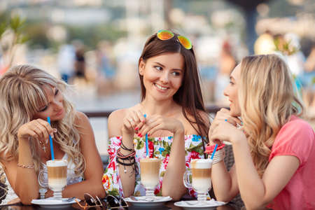 Group Of Women Meeting In Cafe. holidays, tourism, technology and internet - three beautiful girls. Three Women Enjoying Cup Of Coffee In Cafe. Stock Photo