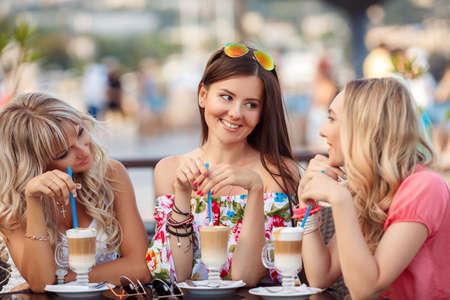 cafe internet: Grupo de Mujeres reunión en el café. vacaciones, turismo, tecnología e internet - tres hermosas niñas. Tres mujeres que disfrutan de una taza de café en café.
