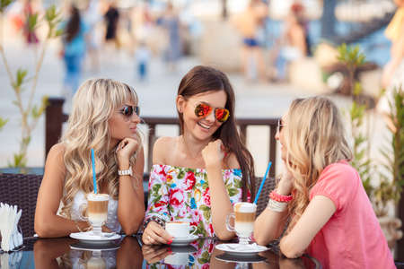 Group Of Women Meeting In Cafe. holidays, tourism, technology and internet - three beautiful girls. Three Women Enjoying Cup Of Coffee In Cafe. 스톡 콘텐츠