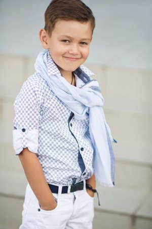 stijlvolle baby boy plezier buiten in het park. Leuke gelukkige jongen kind buitenshuis. schattige kleine stijlvolle jongen in klassieke stijl in de stad. Gelukkig kind poseren buiten. Stockfoto