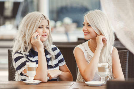 Two young women having coffee break together use smart phone. Happy women using cell phone at sidewalk cafe photo