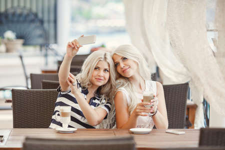 Two young women having coffee break together. Two women using a smart phone photo