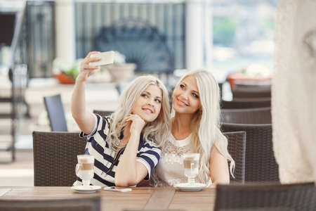 Two young women having coffee break together. Two women using a smart phone