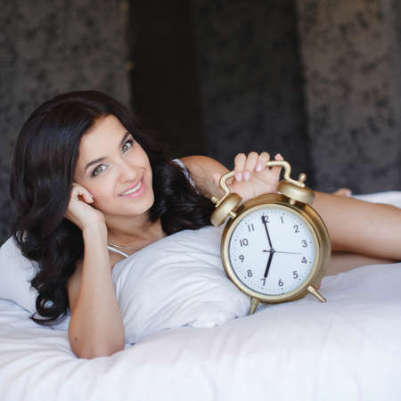 Young woman with alarmclock on the bed at the morning. Relaxed beautiful young woman sleeping in bed at home. photo