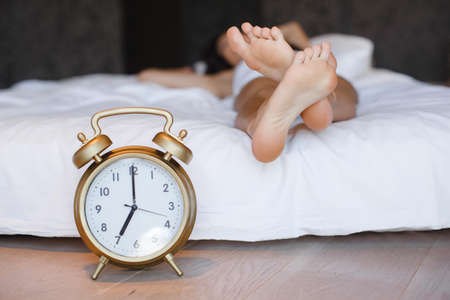 waking up: A clock and the feet of a sleeping woman. Early morning.sleeping young female disturbed by alarm clock early morning on bed