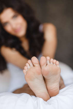 Beautiful feet of a young woman lying in bed close up. Woman Holding her Tired Feet in Hand Sitting on Bed with White Sheets. eet of a woman sleeping on the white linen at home photo