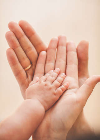 baby hand holding adult finger Stock Photo