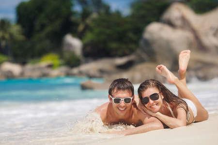 ビーチで楽しく幸せなカップルの写真。