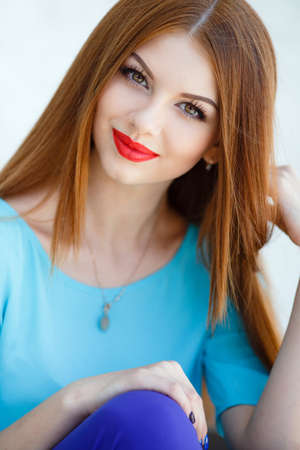 20 s: glamorous portrait of young beautiful woman in bright clothes. red lips. Summer portrait of a beautiful young Caucasian girl with red straight hair. fashion portrait. Stock Photo