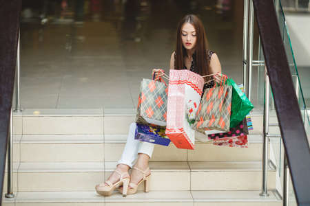 Fashion Shopping Girl Portrait. Beauty Woman with Shopping Bags in Shopping Mall. Shopper. Sales. Shopping Center photo