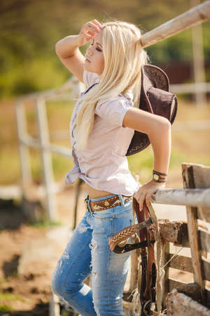 Young american cowgirl woman portrait outdoors. Beautiful natural woman saying hello looking at camera wearing cowboy hat. girl in her twenties outdoor in nature. photo