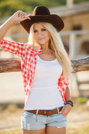 twenties: Young american cowgirl woman portrait outdoors. Beautiful natural woman saying hello looking at camera. girl in her twenties outdoor in nature.