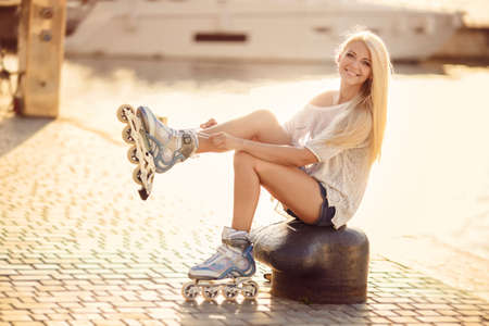 Young girl enjoys skating on roller skates in the park. Woman outdoors. Beautiful girl on roller skates in the park.