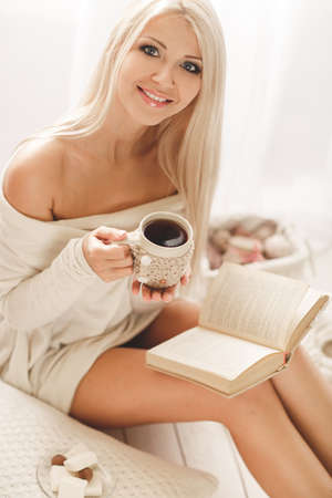 Soft portrait of a blonde with gray eyes, drinking hot coffee and reading a book at home. Young beautiful woman in warm knitted clothes handmade home. Fall, winter season. photo