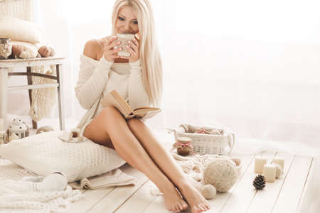 Soft portrait of a blonde with gray eyes, drinking hot coffee and reading a book at home. Young beautiful woman in warm knitted clothes handmade home. Fall, winter season. Stock Photo