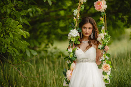 Portrait of the beautiful bride in the white wedding dress sitting on a swing in the open air in green park in the summer photo