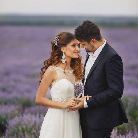 Closeup portrait of the bride and groom in wedding attire, enjoying the love Sunny summer day on the blooming lavender fields. photo