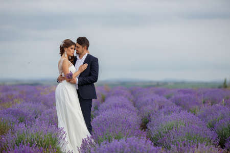 A young couple in love bride and groom, wedding day in summer. Enjoy a moment of happiness and love in a lavender field. Bride in a luxurious wedding dress on a background bright blue sky . photo