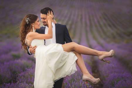 A young couple in love bride and groom, wedding day in summer. Enjoy a moment of happiness and love in a lavender field. Bride in a luxurious wedding dress on a background bright blue sky with clouds. photo