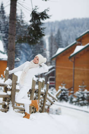 hobby hut: Beautiful young woman in a white sports suit in the Swiss Alps at winter resort. Stock Photo