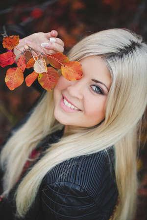 Beautiful blonde woman walks in autumn park photo