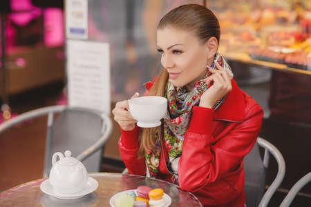 cabelo amarrado: Modelo da mulher com um copo da bebida quente. Caf�s, Europa, pastelaria francesa, uma bela jovem - morena de cabelo amarrado para tr�s, com cinza - olhos verdes, vestindo uma jaqueta vermelha e um len�o ao redor do pesco�o, bebendo ch� em uma mesa em um caf�.