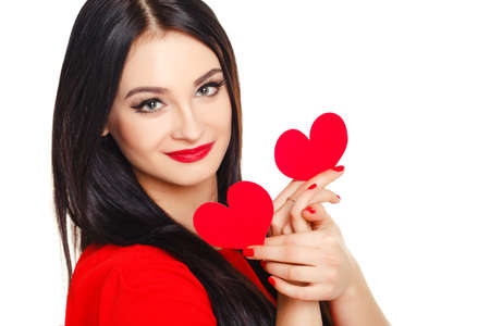 ideally: Beautiful brunette with long straight hair and bright make-up, dressed in a red dress, holding a small red heart, isolated on white background.