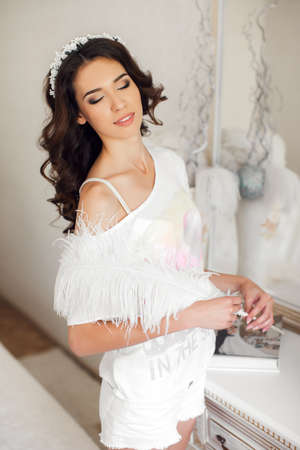 Young bride - brunette with long curly hair, bridal wreath on his head in the night white shirt with a large white and fluffy pen in hand, preparing for the wedding night in front of a mirror in a beautiful white bedroom. photo