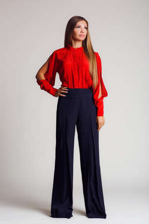 informal clothing: Portrait-style - professional model on a light background.A young woman, a brunette with long straight hair, with gray - green eyes, light makeup, a mole on his left cheek,makes the show a bright red blouse with slits on the sleeves and black wide pants, Stock Photo