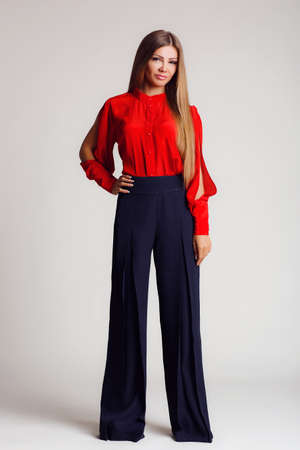 known: Portrait-style - professional model on a light background.A young woman, a brunette with long straight hair, with gray - green eyes, light makeup, a mole on his left cheek,makes the show a bright red blouse with slits on the sleeves and black wide pants, Stock Photo
