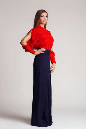 slits: Portrait-style - professional model on a light background.A young woman, a brunette with long straight hair, with gray - green eyes, light makeup, a mole on his left cheek,makes the show a bright red blouse with slits on the sleeves and black wide pants, Stock Photo
