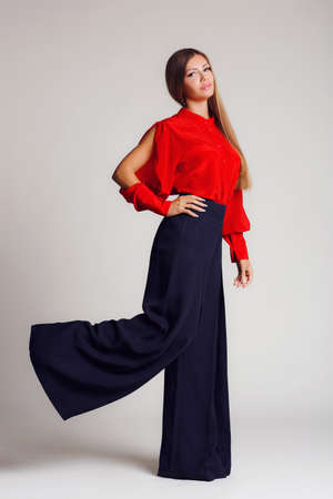 Portrait-style - professional model on a light background.A young woman, a brunette with long straight hair, with gray - green eyes, light makeup, a mole on his left cheek,makes the show a bright red blouse with slits on the sleeves and black wide pants, Stock Photo