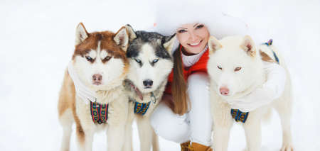Portrait of a beautiful woman with Siberian huskies - Husky.Beautiful woman with green eyes, white fluffy in winter hat and white pants and red jacket, a light - brown shoes, posing with three husky sled dogs with brown, gray and white color on the backgr photo