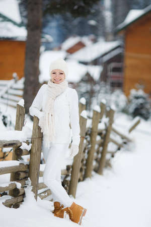 ski lodge: Portrait of a beautiful woman at a ski resort in winter.Young beautiful woman in a white track suit with a white scarf around his neck and a white winter hat, with light make-up, standing at the wooden fence, posing against the backdrop of wooden houses a Stock Photo