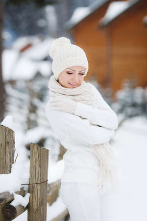 Portrait of a beautiful woman at a ski resort in winter.Young beautiful woman in a white track suit with a white scarf around his neck and a white winter hat, with light make-up, standing at the wooden fence, posing against the backdrop of wooden houses a photo