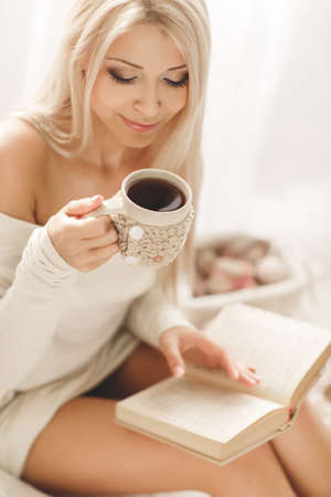 Young beautiful woman - blonde, wearing a warm knit short dress handmade, light - beige, reading a book with a cup of coffee in his hand lying on the couch at home in the bedroom. photo