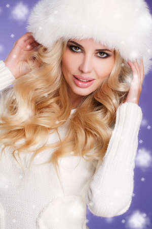 Winter beauty - portrait of a young woman.Studio portrait of a young woman - blonde with long curly hair and brown eyes, a white fluffy fur hat, a white scarf and a white knitted sweater with a nice make-up on a blue background, the snow falls. photo