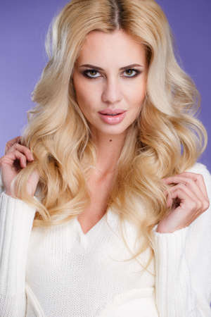 Close-up - a portrait of a beautiful woman.Studio portrait of a young woman - blonde with long curly hair and brown eyes, wearing a white knitted sweater with a nice make-up on a light purple background, beautiful smile and full lips. photo