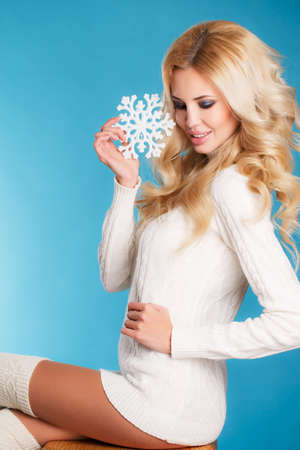 Portrait of a beautiful blonde with snowflake hands.Studio portrait of a young woman - blonde with long curly hair and brown eyes, wearing a white knitted sweater with a nice make-up on a light blue background, holding a large white snowflake, snow falls. photo