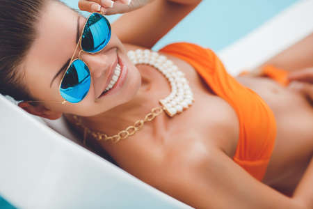swimsuit model: Beautiful young woman with brunette hair gathered at the nape of the neck, sun glasses blue mirror glasses, orange bikini, neck wearing necklace, posing for a photograph lying on a sun lounger.