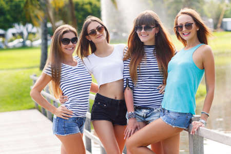 Image of four young attractive girls having fun outdoors. Young and attractive girlfriends have fun in park. Four women n summer park photo