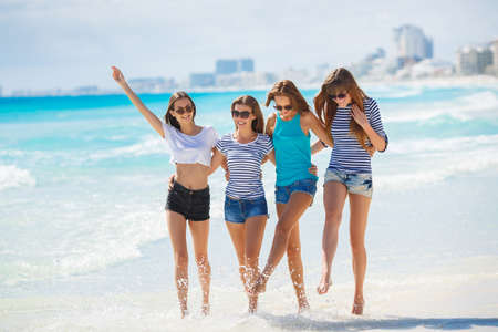 girl in shorts: Beautiful girls are photographed on a tropical resort on the background of the beach and ocean.Four beautiful young girls brunette long straight hair, wearing shorts and t-shirts, sun glasses, with a beautiful smile, having fun and having fun, posing for