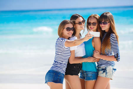 Beautiful girls are photographed on a tropical resort on the background of the beach and ocean.Four young beautiful girls - brunette, long straight hair, in shorts and T-shirts, sun glasses, with a beautiful smile, photographed on a smartphone on the back Фото со стока