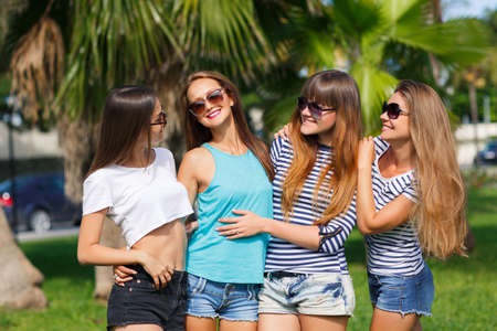 Beautiful girls are photographed on a tropical resort on a background of green nature.Four young beautiful girls - brunette, long straight hair, in shorts and T-shirts, sun glasses, with a beautiful smile, photographed on a smartphone on a background of t photo