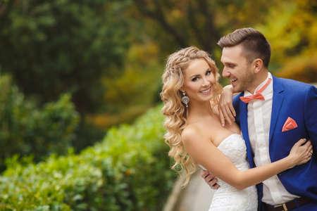matrimonio feliz: La novia y el novio en el día de la boda caminando al aire libre en la naturaleza de primavera. Pareja de novios, mujer feliz recién casado y el hombre abrazando en parque verde. Amantes de la boda al aire libre. Los novios