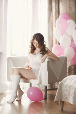 night shirt: Pregnant woman in a white nightgown with balloons. Beautiful young pregnant woman in a white night shirt and white socks, long curly hair,sitting on a chair in the bedroom, supports his stomach, putting his hand on him, wears a ring on his left hand, on a Stock Photo