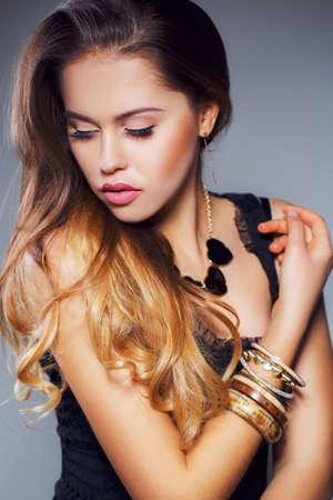 ojos marrones: Joven y bella mujer con el pelo largo y marr�n ojos rojos, vestido con una cadena del cuello vestido sin mangas negro con corazones negros en la mano derecha lleva pulseras, maquillaje hermoso, aislado en gris. Foto de archivo