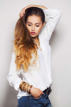 belts: Beautiful young woman with long - red hair and brown eyes, wearing a light - blue jeans with holes in the knees and a white shirt at the neck is a gold chain on his right hand wears bracelets, beautiful makeup, isolated on gray. Stock Photo