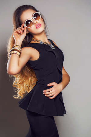 sleeveless dress: Beautiful young woman with long - red hair, a round sun glasses, wearing a black sleeveless dress at the neck is a beautiful necklace, on the right hand wears bracelets, beautiful makeup, isolated on gray. Stock Photo